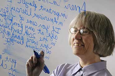 """Writing is powerful,"" says Deb Brandt, professor of english, who has studied the importance of writing literacy in education and business. Here, Brandt writes and revises the text of the article accompanying this photograph by writing it out on a piece of glass.© UW-Madison University Communications 608-262-0067Photo by: Michael Forster RothbartDate: 9/05 File#: D100 digital camera frame 11485"
